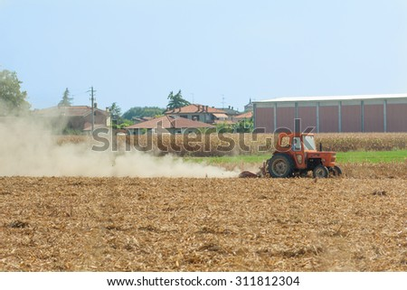 FERRARA, Italy - August 22, 2015: Farmer plows his field with the tractor, on a hot summer day, in Ferrara, Italy - stock photo