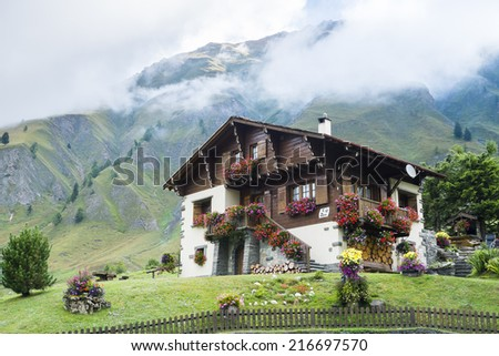 FERRET, SWITZERLAND - AUGUST 30: Beautiful chalet decorated with flowers and with mountains in the background. The village is a stage of the Mont Blanc tour. August 30, 2014 in Ferret. - stock photo