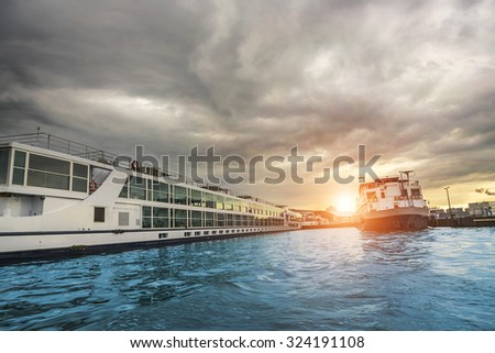 Ferries on the Amstel river at sunset in Amsterdam, Netherlands.  - stock photo