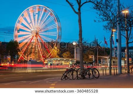 Ferris wheel and street traffic in Zurich - stock photo