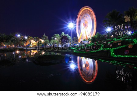Ferris wheel at night view with water reflection - stock photo