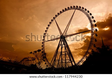 Ferris Wheel at sunset. Some Chinese words in the photo mean roller coaster and not an ad. - stock photo