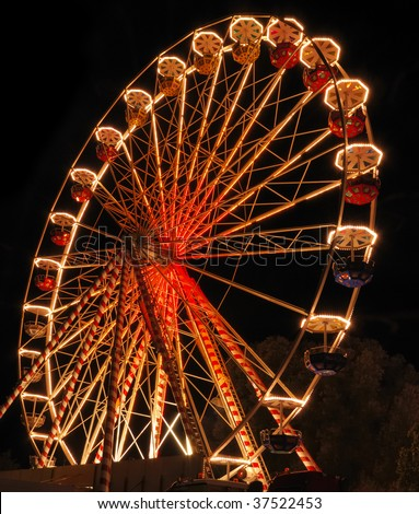 Ferris wheel at the fair ground at night. - stock photo