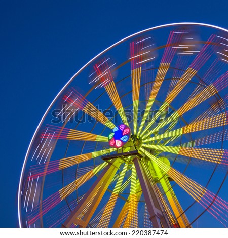 Ferris Wheel Carousel on a dark blue sky background. Long time exposure. - stock photo