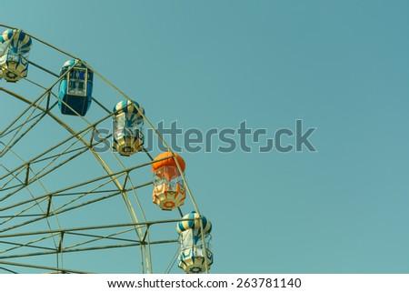 Ferris wheel in blue sky on retro and vintage tone - stock photo