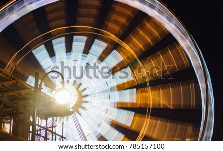 Ferris Wheel in motion at night with a lantern on the first plan