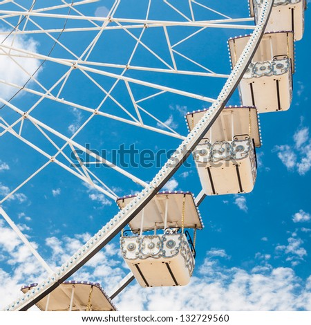 Ferris wheel of fair and amusement park.  White clouds in the blue sky in background.