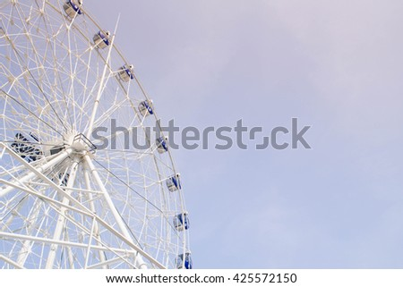 ferris wheel on blue sky and white cloud in soft color filter - stock photo