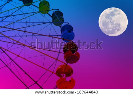 Ferris wheel on the full moon colorful sky background - stock photo
