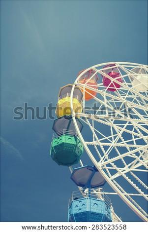 Ferris wheel over blue sky - retro styled photo - stock photo