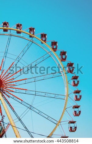 Ferris wheel with blue clear sky on the background