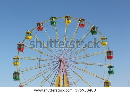 Ferris wheel with color cabins against the blue sky  - stock photo