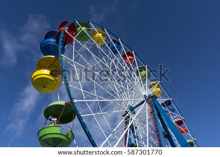 Ferris wheel with colored cabins on the blue sky background, Sunny day, clouds, ride, fair, fun