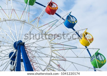 Ferris wheel with colored cabins with blue cloudy sky as background