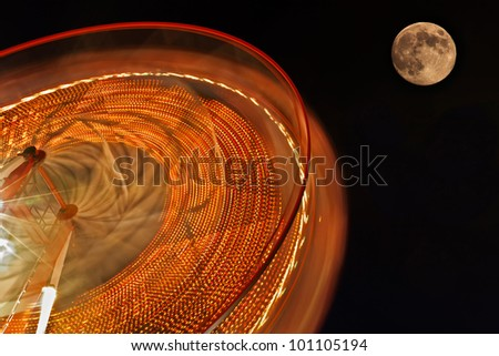 Ferris Wheel with full moon in background. - stock photo
