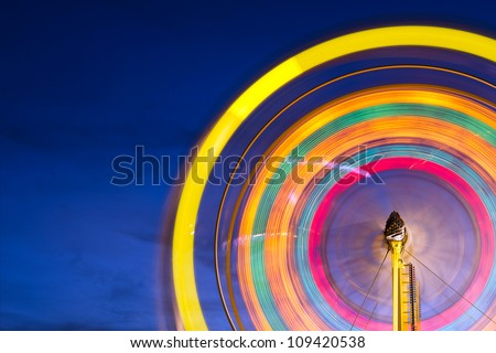Ferris wheel with motion blurred lights with copy space - stock photo