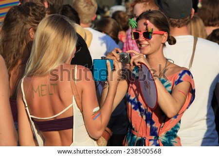 FERROPOLIS, GERMANY - JULY 18, 2014: Hipster girls taking photos of each other at MELT Festival on July 18, 2014 in Ferropolis. - stock photo