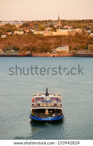 Ferry boat in river in Quebec City at sunset. - stock photo