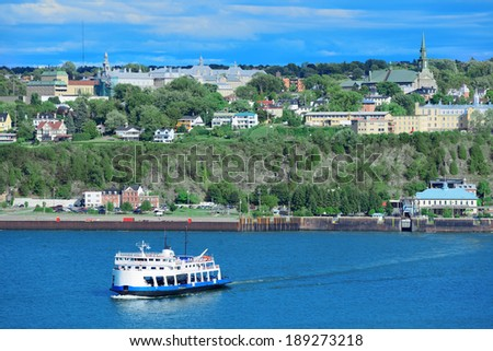 Ferry boat in river in Quebec City with blue sky. - stock photo