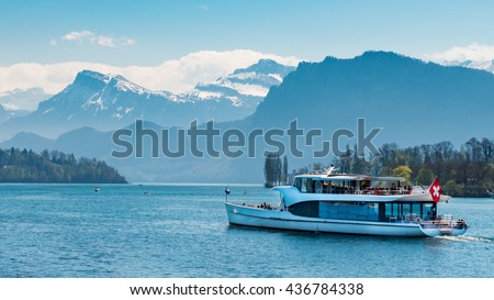 Ferry boat with red swiss flag carry passengers on Lake Lucerne (Vierwaldstattersee) Switzerland. Motor Cruise Ship Waldstatter sail from Weggis full of tourist people under clear blue sky in summer