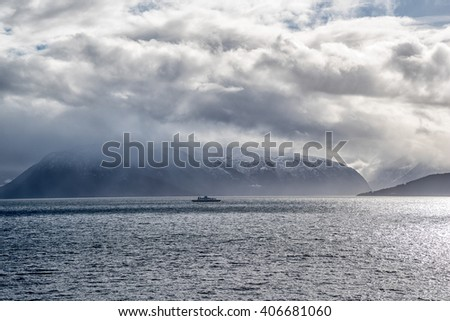 Ferry in fjord surrounded by Mountains - stock photo