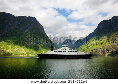 Ferryboat is sailing by the fjord. The ship is navigated along the cliffs - stock photo