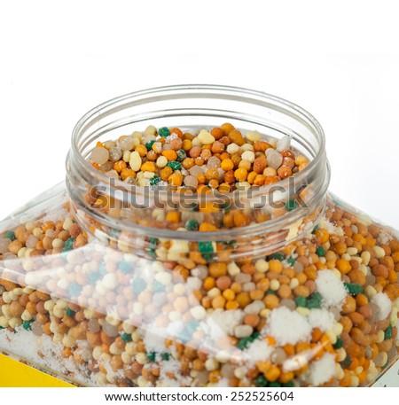 Fertilizer granules in plastic bottle - stock photo