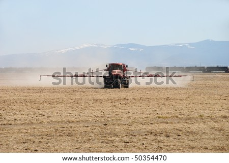 Fertilizer Spreader working an field in Klamath Falls area.  Rig is from Basin Chemical and Fertilizer Company - stock photo