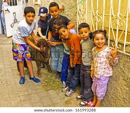 FES, MAROCCO - October 15 2013 : Kids with their sheep on Eid al-Adha. The festival is celebrated by sacrificing a sheep or other animal and distributing the meat to relatives, friends, and the poor. - stock photo
