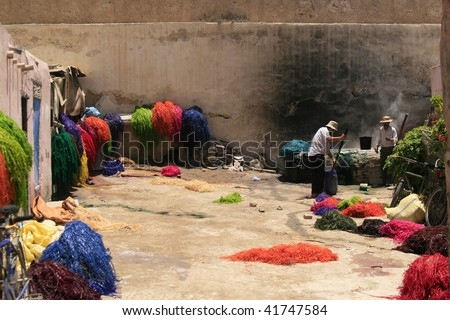 FES, MOROCCO - JUNE 9: Men coloring dried hay with bright dye on June 9, 2008 in Fes, Morocco. The dye used is very poisonous and often creates health issues for workers - stock photo