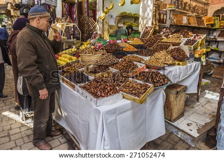 FES, MOROCCO - 26 MARCH 2015: Unidentified people in the old medina of Fes. Dry fruits are one of the most common food stalls in the streets - stock photo