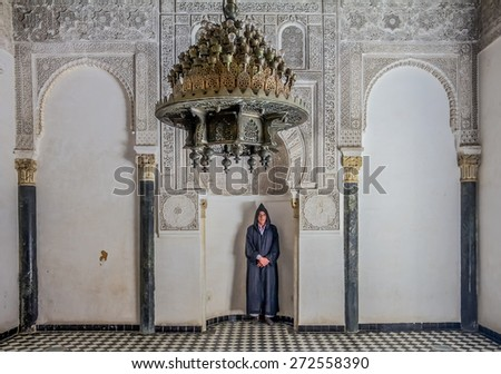 Fes, Morocco - May 11, 2013: Man in berber clothing in an alcove in the inner courtyard of the 14th century  El Attarine Medersa in Fez, Morocco - stock photo