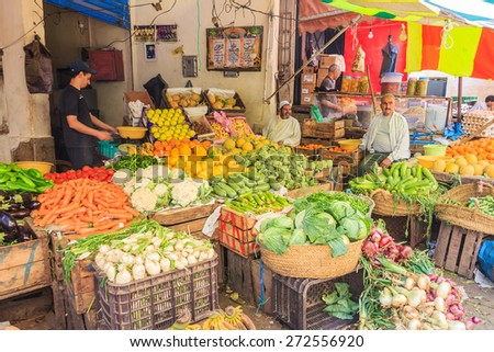 Fes, Morocco - May 11, 2013: Men selling vegetables at a stand in the souk, Moroccan market in the medina - stock photo