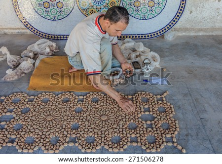 Fes, Morocco - May 11, 2013: Moroccan mozaic artist at work in a pottery shop - stock photo