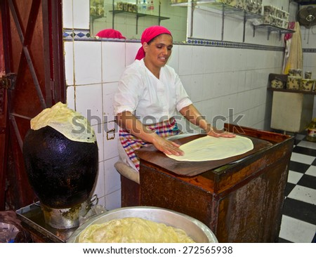 Fes, Morocco - May 11, 2013: Woman making Moroccan crepes in a souk in Fez Medina - stock photo