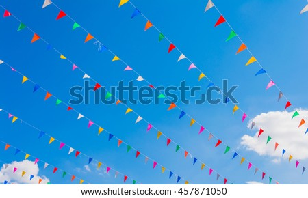 festival flag line with blue sky in background on day time . - stock photo