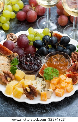festive appetizers - cheeses, fruits and jams on plate, vertical, closeup - stock photo