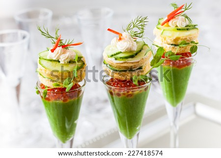 festive appetizers with avocado puree, red caviar and cucumber sandwiches - stock photo