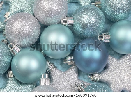 Festive background of aqua turquoise pale blue christmas glitter baubles and stars on a pale aqua blue material tablecloth background.