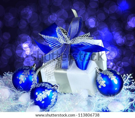 festive balls with gift box on snow - stock photo
