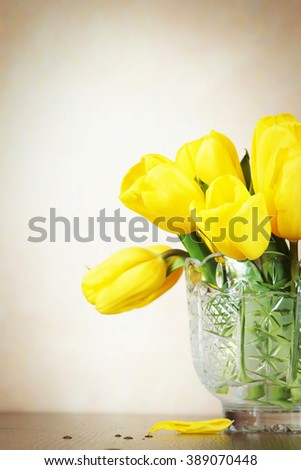 Festive beige background with a bouquet of bright yellow tulip flowers in the crystal vase - stock photo