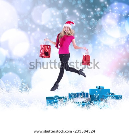 Festive blonde carrying gift bags against light glowing dots on blue - stock photo