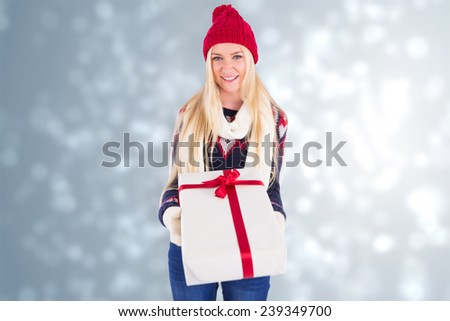 Festive blonde holding a gift against light design shimmering on silver