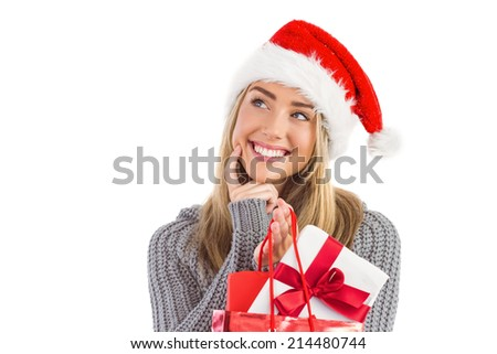 Festive blonde holding christmas gift and bag on white background - stock photo