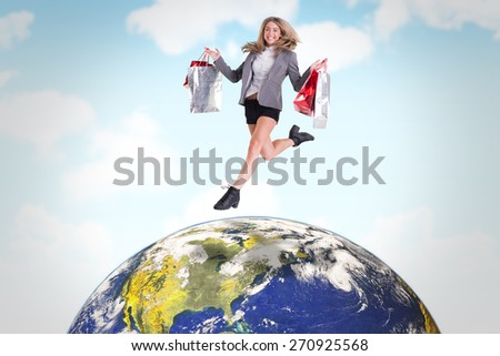 Festive blonde jumping with shopping bags against blue sky - stock photo