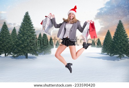 Festive blonde jumping with shopping bags against snowy landscape with fir trees - stock photo