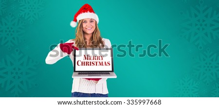 Festive blonde pointing to laptop against green snowflake background - stock photo