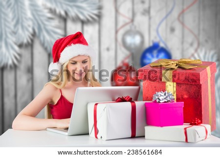 Festive blonde shopping online with laptop against christmas baubles hanging over wood - stock photo