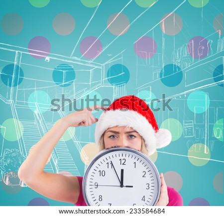Festive blonde showing a clock against blue vignette - stock photo