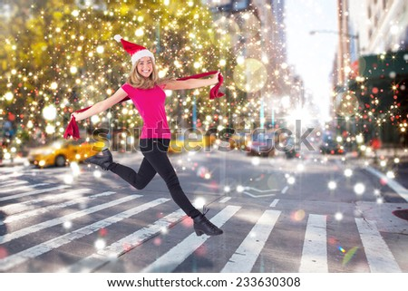 Festive blonde skipping and smiling at camera against blurry new york street - stock photo
